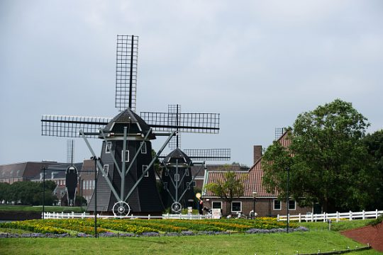 Windmills stand at the Dutch-themed Huis Ten Bosch amusement park, operated by Huis Ten Bosch Co., in Sasebo, Nagasaki Prefecture, Japan, on Thursday, July 16, 2015. Huis Ten Bosch is spread across 1.52 million square meters (376 acres), about twice the size of Tokyo Disneyland, according to its website. Photographer: Akio Kon/Bloomberg via Getty Images
