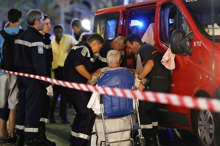 "TOPSHOT - Rescue workers help an injured woman to get in a ambulance on July 15, 2016, after a truck drove into a crowd watching a fireworks display in the French Riviera town of Nice. A truck ploughed into a crowd in the French resort of Nice on July 14, leaving at least 60 dead and scores injured in an ""attack"" after a Bastille Day fireworks display, prosecutors said on July 15.  / AFP / Valery HACHE        (Photo credit should read VALERY HACHE/AFP/Getty Images)"