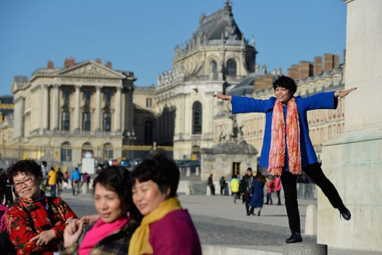 PARIS, FRANCE - NOVEMBER 15:  Chinese tourists pose for a picture with Versailles castle in the background on November 15, 2015 in Paris, France.  As France observes three days of national mourning members of the public continue to pay tribute to the victims of Friday's deadly attacks. A special service for the families of the victims and survivors is to be held at Paris's Notre Dame Cathedral later on Sunday. (Photo by Pascal Le Segretain/Getty Images)